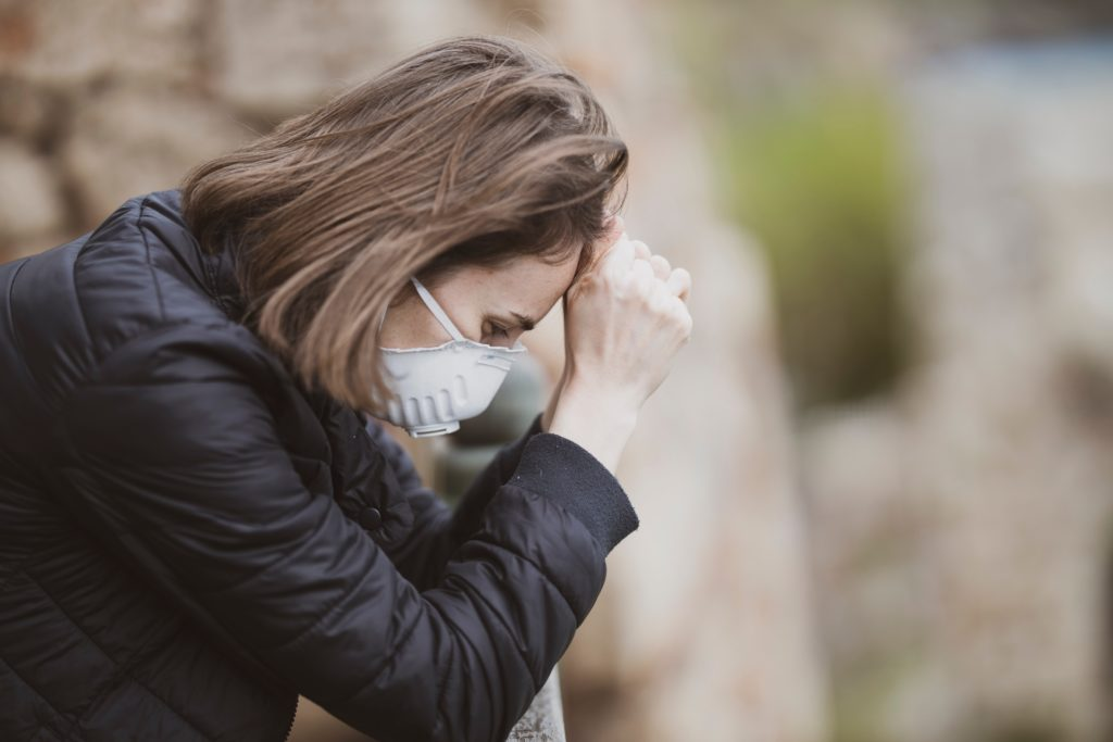 Stressed woman in face mask leaning forward outside.